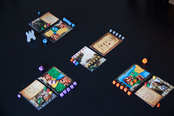 A three-player game of Tiny Epic Kingdoms ready to re-enact Warcraft (Orcs vs. Humans vs. Undead)
